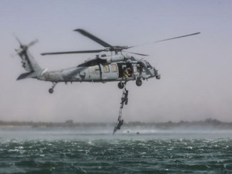 5th SFG Soldiers ascend a rope ladder while conducting maritime exfilitration.