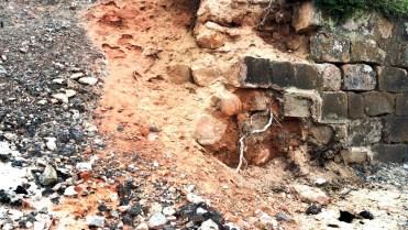 Mauer, die in Lehm und Geröll übergeht