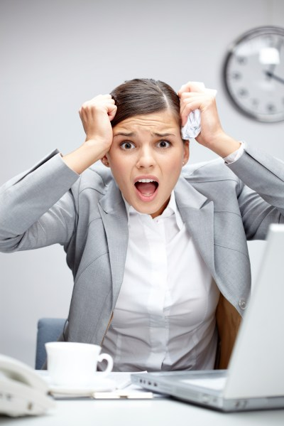 Image of young employer touching her head in frustration at workplace