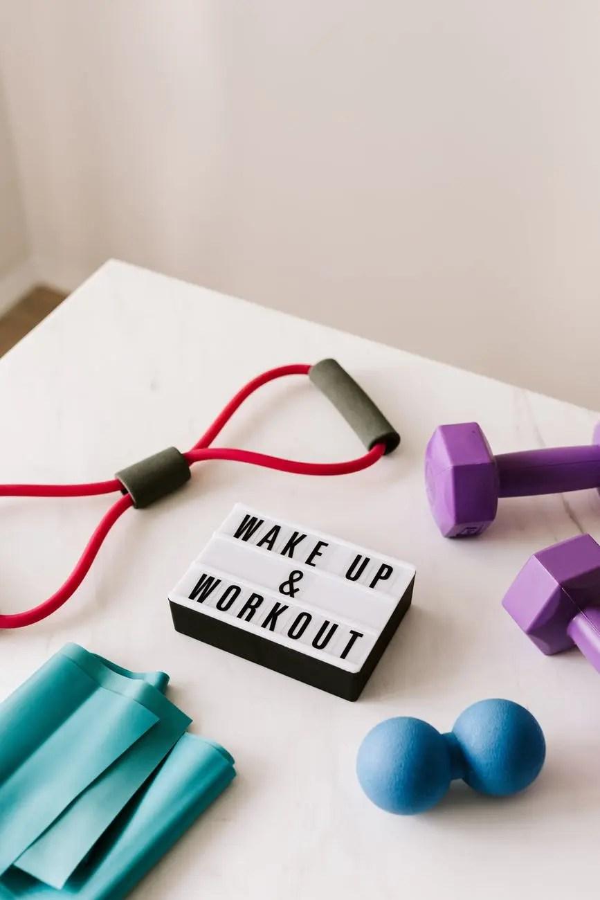 wake up and workout slogan on light box among sports equipment