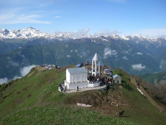A Church in front of Georgian mountains with snowy peaks