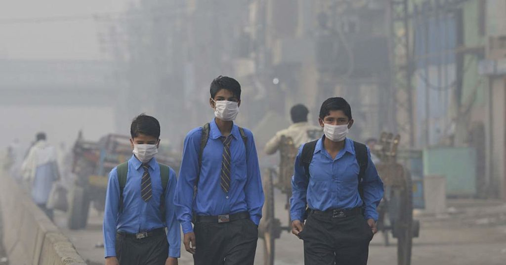 Air pollution in Pakistan. Three boys with face masks are walking down a polluted road.