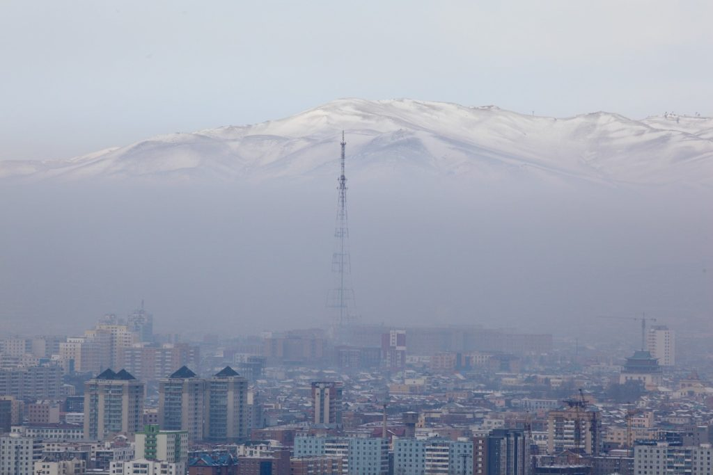 Smog over a city in Mongolia with mountains in the background.