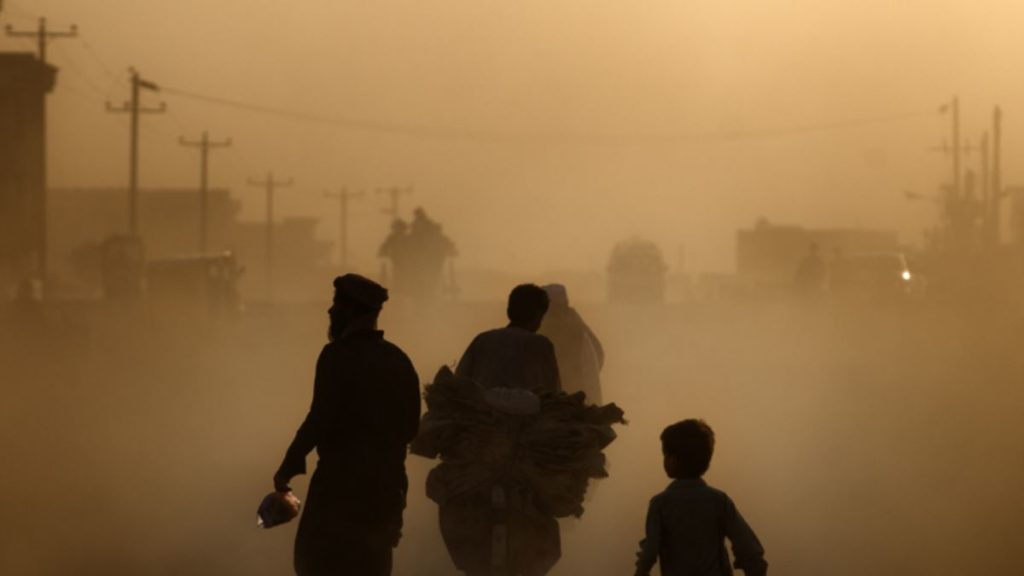 A few people walk and drive through thick smog in Kabul, Afghanistan