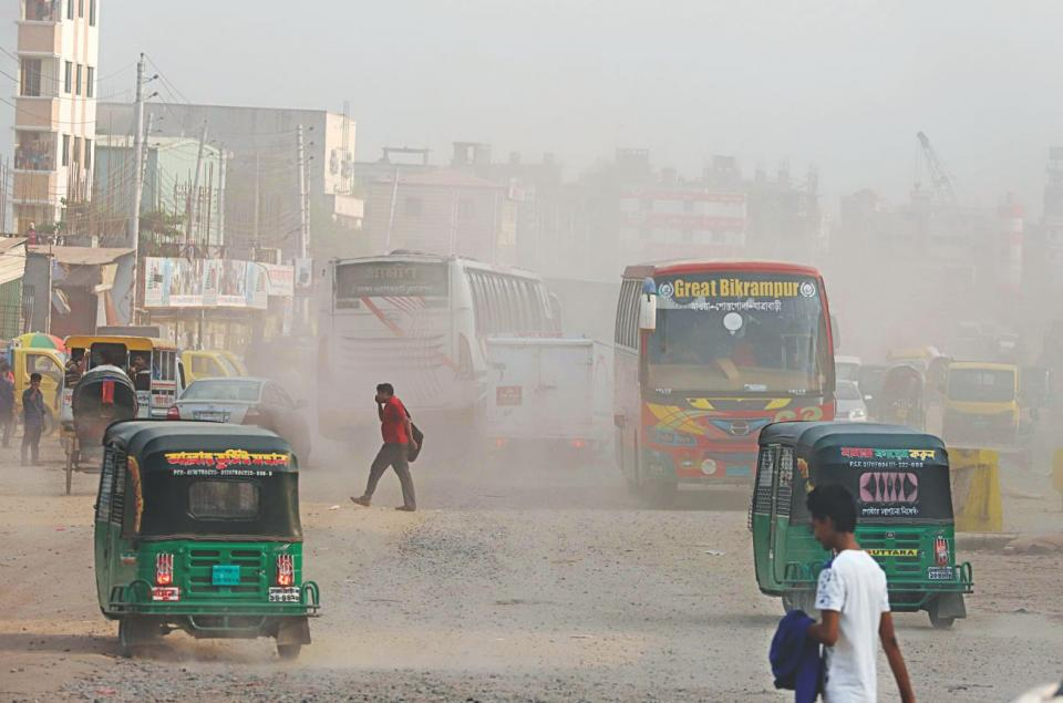 A busy street in Bangladesh. Humans and busses on a dusty road.