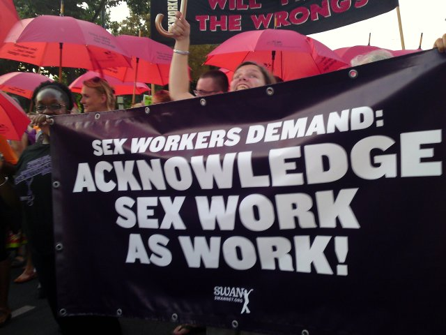 Marchers holding a banner that reads SEX WORKERS DEMAND: ACKNOWLEDGE SEX WORK AS WORK!