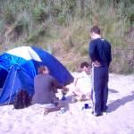 Preparando la cena sulla griglia portatile a Wicklow, in campeggio sulla spiaggia