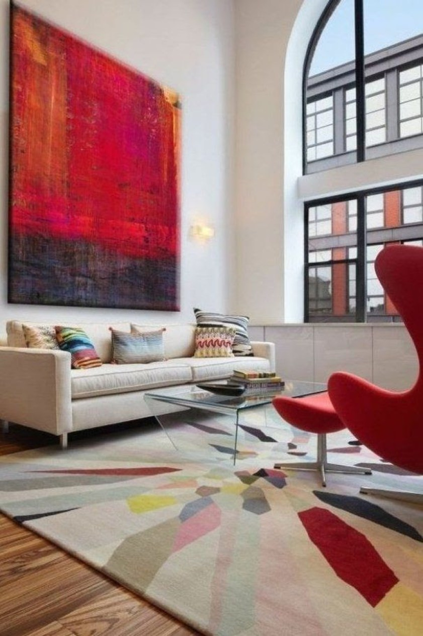 Red art, chair and in a rug, in a modern setting.
