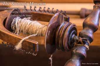 A close up view of part of the working spinning wheel at the museum