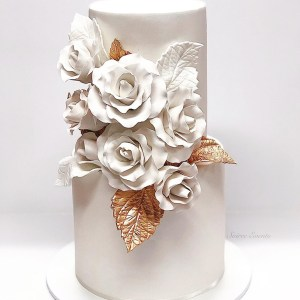 white and gold wedding cake with sugar roses