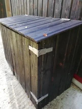 Un coffre en bois brûlé pour cacher des bouteilles de gaz à l'extérieur de la maison