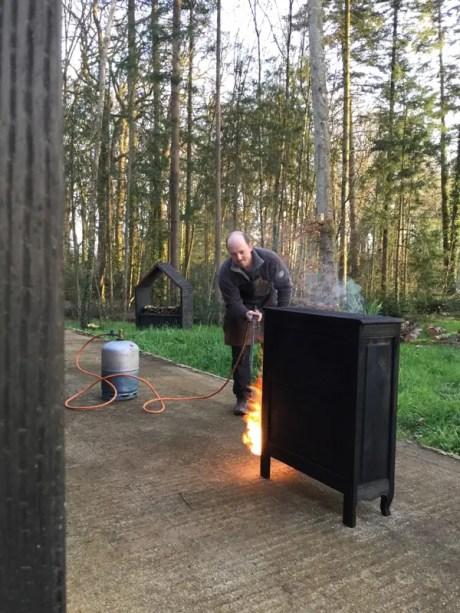 Petit meuble d'appoint en chêne massif en cours de brûlage en extérieur avec la méthode du Shou Sugi Ban ou Yakisugi