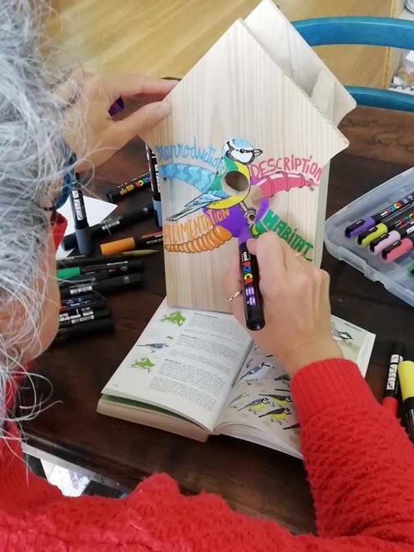 Sophie Le Penher dessine la carte mentale sur le nichoir à mésange