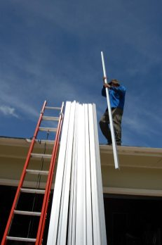 Tim grabs one of the 14 railings that our 5.5 kW, 26-panel system will be mounted on.