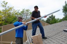Tim (left) hands off a railing to Joel (right) on the upper part of our roof.
