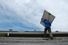 Tim hoists another 35-pound solar panel high up onto our roof.