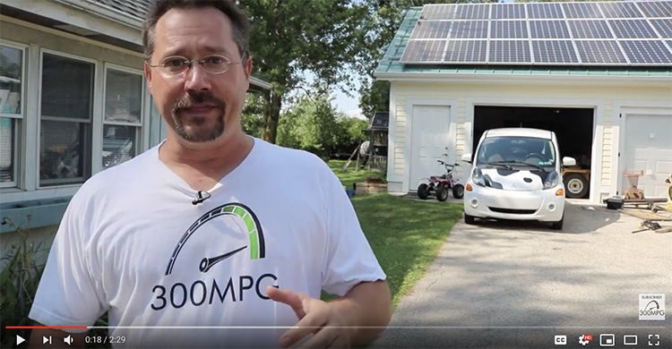 man standing in front of electric car and home solar system