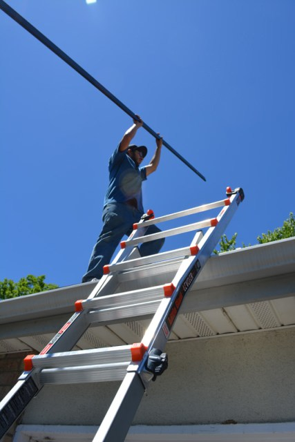 Vincent handles a solar railing on the garage roof on Day 1.