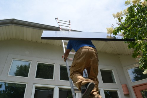 Shane heads up ladder with the first solar panel.