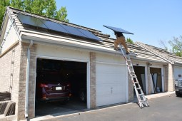 Shane brings up a solar panel up to the garage units on Day 5 of the installation.