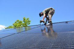Vincent of Sopris Solar secures solar panels together on the south roof of the HCC Common House.