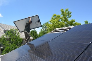 Vincent heads up to the HCC Common House south roof with the last of 63 310 watt Mission Solar solar panels that are part of the 19.6 kW of solar the community added.