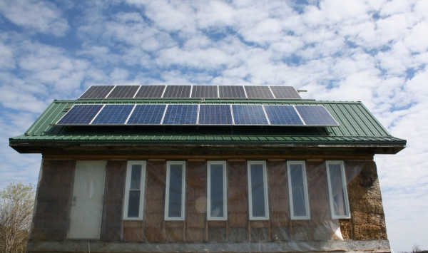 strawbale buidling with solar modules mounted to roof.