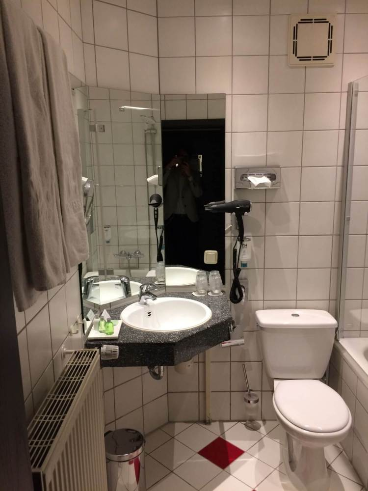The sink, toilet, mirror and hair dryer