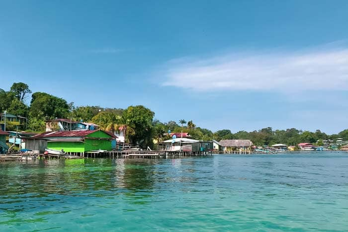 Old Bank on isla bastimentos with clear blue water blue sky and brightly painted houses along the shoreline