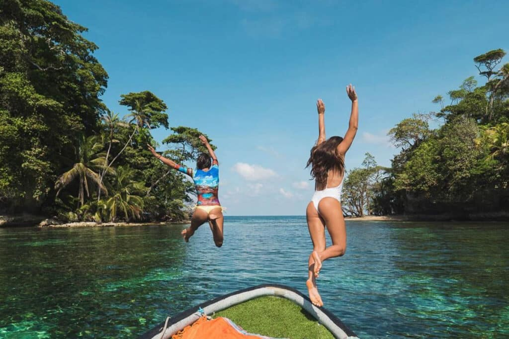 bird island women jumping into water from mono loco surf school in Bocas del Toro Panama