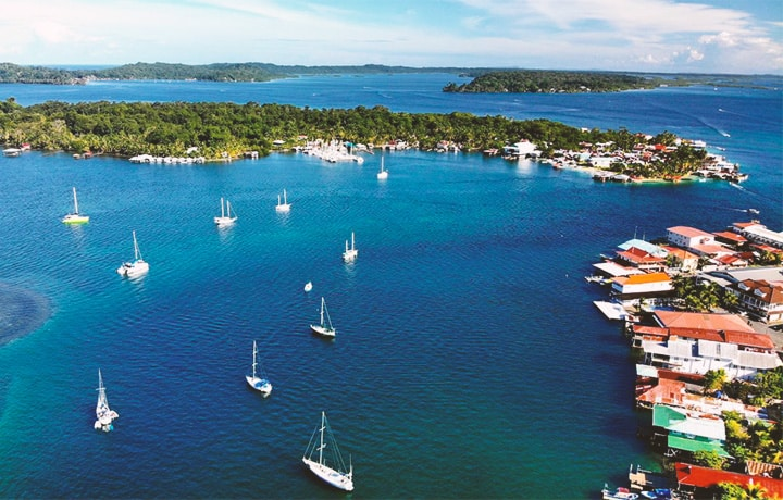 Drone view of sailboats and blue water above bocas town, isla carenero, isla bastimentos, and isla solarte in bocas del toro panama.