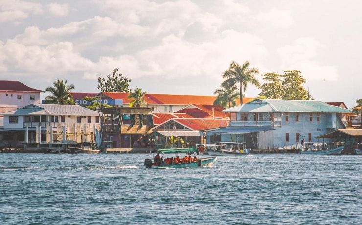 a light sky with colorful buildings that line the shores of bocas town with a green water taxi boat full of people driving in the blue ocean.