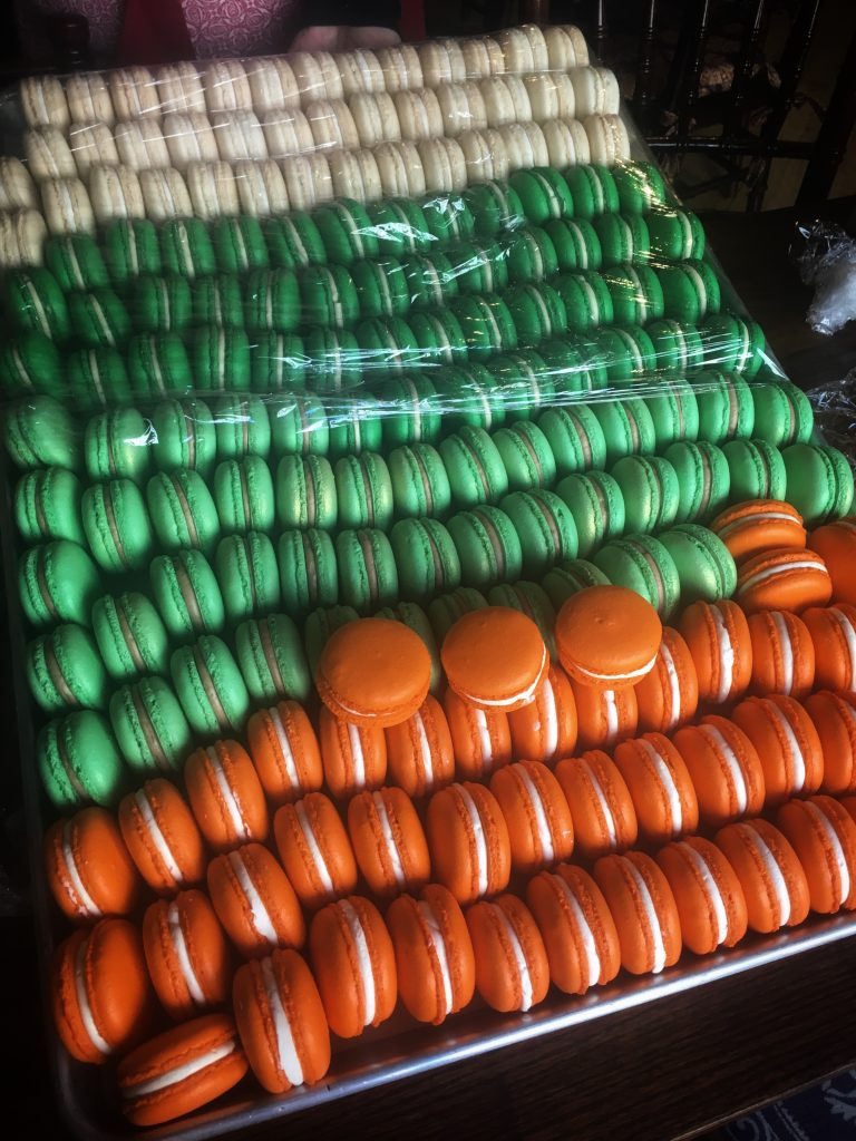 A large sheet tray of french macarons wrapped in plastic wrap.