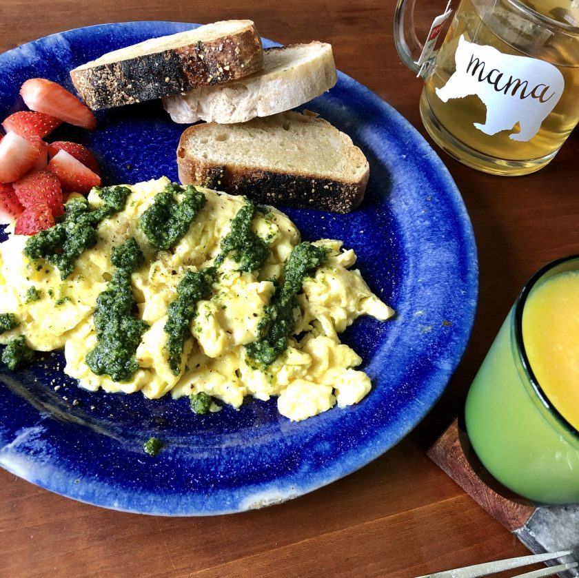 A breakfast plate of eggs with a drizzle of pesto over the top, served with fresh strawberries, toast, orange juice and tea.