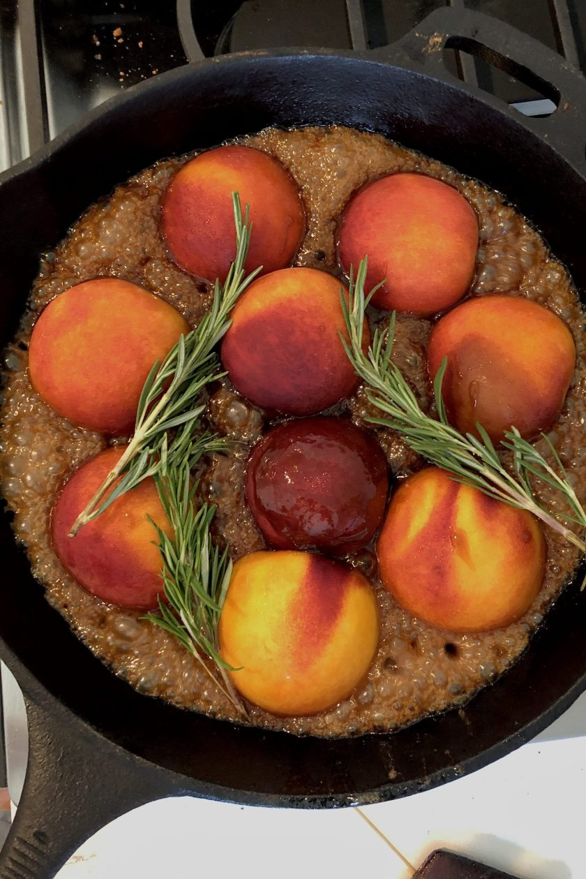 Peaches cooking in a cast iron skillet with a bubbling caramel and a few sprigs of rosemary.
