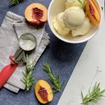 Roasted peach and rosemary ice cream in a bowl with an ice cream scoop