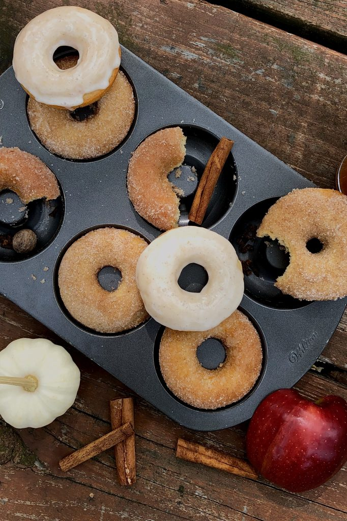 baked apple cider donuts in a pan with cinnamon sugar coating