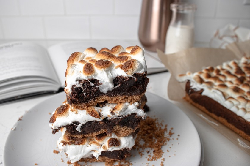 sticky s'mores brownies sitting on a plate with milk and a cook book