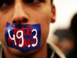 epaselect epa05298508 A young man covers his mouth with a 49.3 sticker as hundreds of protesters gather in front of French National Assembly in Paris, France, 10 May 2016, following the use by the French government of the 49.3 article of the constitution to pass the controversial labor reform law at Parliament. Article 49.3 of the French constitution authorizes the government to pass a bill without putting it for a vote at the French Parliament afterwards and it engages the responsibility of the government if ever the 49.3 is censored and forced to be voted and denied.  EPA/YOAN VALAT (MaxPPP TagID: epalivetwo140473.jpg) [Photo via MaxPPP]