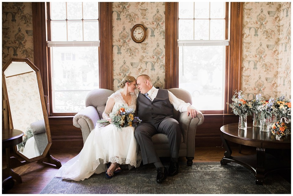 Wedding couple snuggling on couch on the day of their wedding.