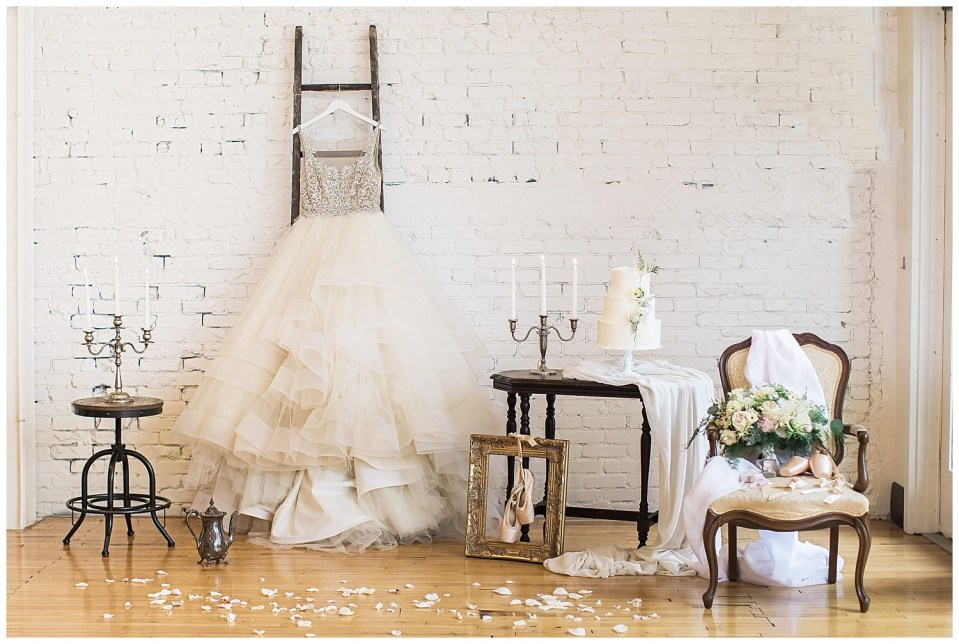 Background containing a chandelier, a wedding dress hanging from a ladder, a table with a cake and a chair with a wedding bouquet during a fine art wedding photoshoot in South Dakota.