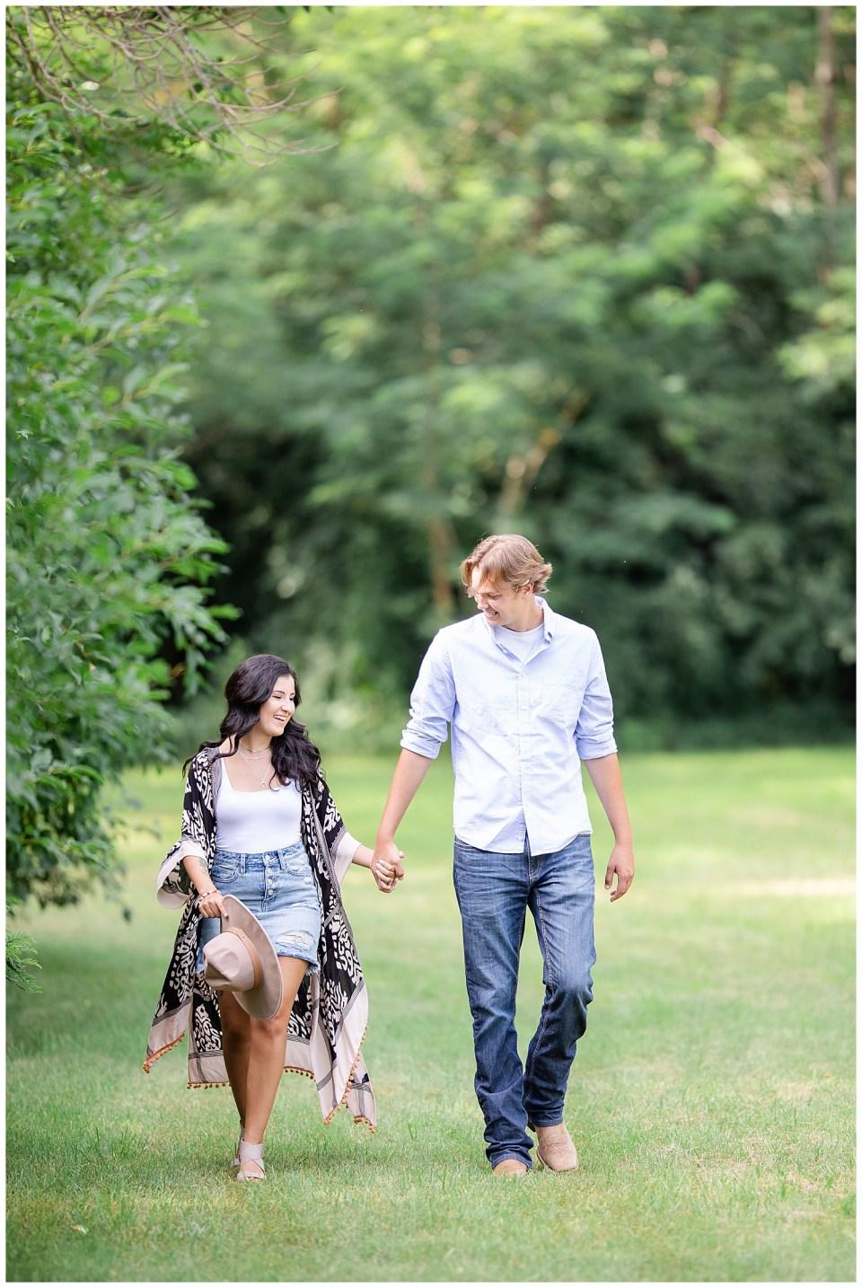 Couple walking together at Wall Lake, South Dakota during engagement session at sunset