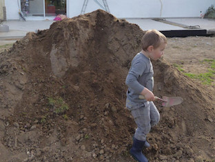 Tas de terre avec un enfant qui joue, équipé de bottes et d'une pelle.