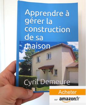 """Livre broche """"apprendre à gérer la construction de sa maison"""" de l'auteur Cyril DEMEURE tenu dans sa main avec logo AMAZON"""