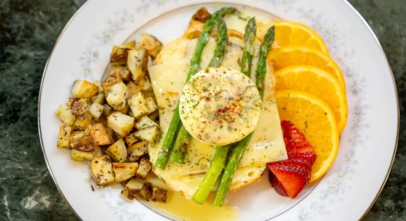Close up view of eggs benedict dish topped with asparagus with country potatoes on one side and sliced strawberries and oranges on the other side