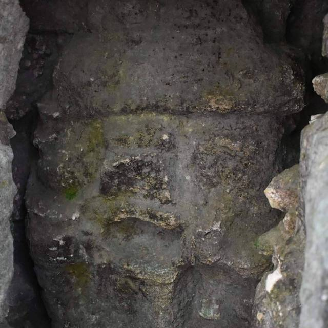 Hidden mask. It was covered up by a wall. When a new Lord built a pyramid he would cover up the older motifs.