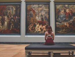 Une femme assise regardant des tableaux