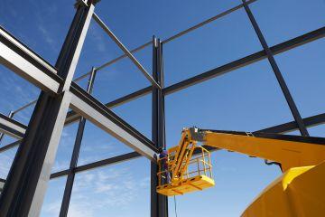 Welder working from cherry picker on warehouse construction