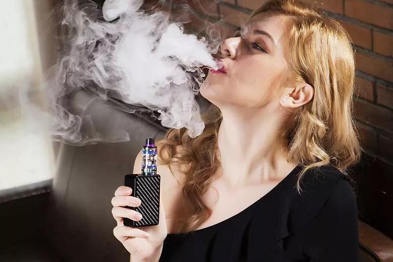 une cliente vapote sa cigarette electronique dans le magasin