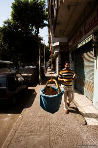 An Egyptian man walks by a hanging basket lowered from a window in anticipation of a delivery